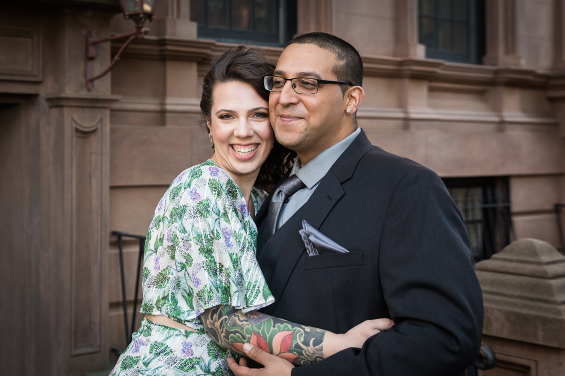 Couple hugging in front of brownstone during a Brooklyn Heights Promenade engagement photo shoot
