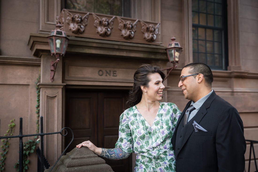 Couple standing in front of brownstone during a Brooklyn Heights Promenade engagement photo shoot