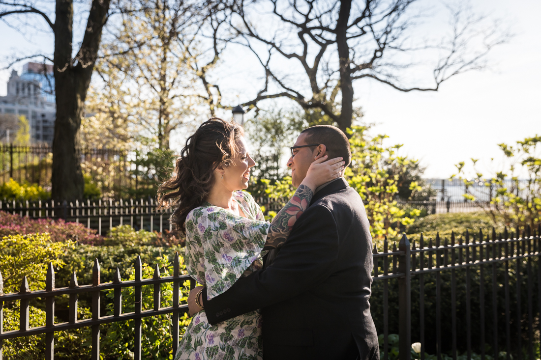 Couple looking at each other in front of garden during a Brooklyn Heights Promenade engagement photo shoot