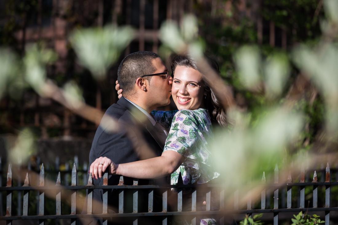 View through plants of man kissing woman's cheek