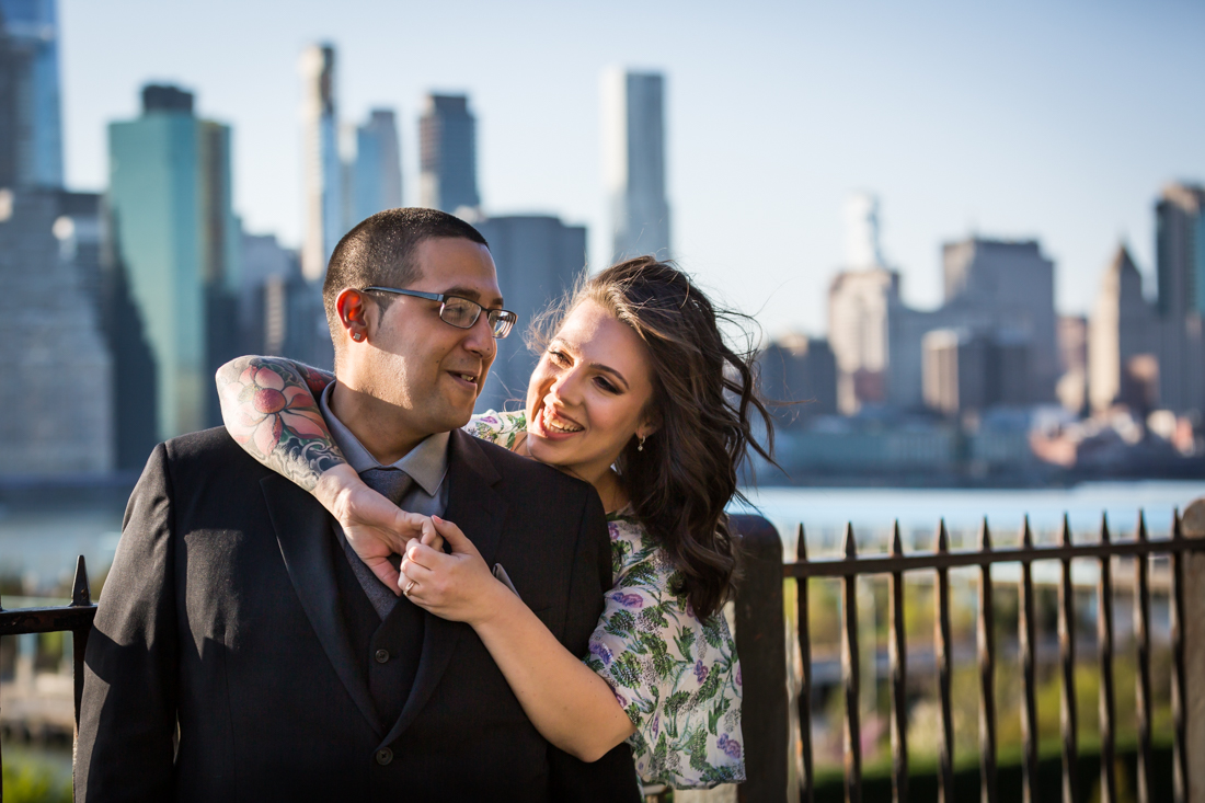 Woman hugging man from behind during a Brooklyn Heights Promenade engagement photo shoot