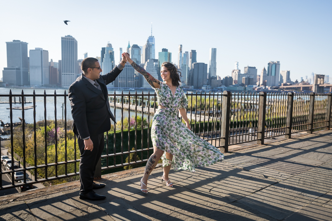 Couple dancing with arms raised during a Brooklyn Heights Promenade engagement photo shoot