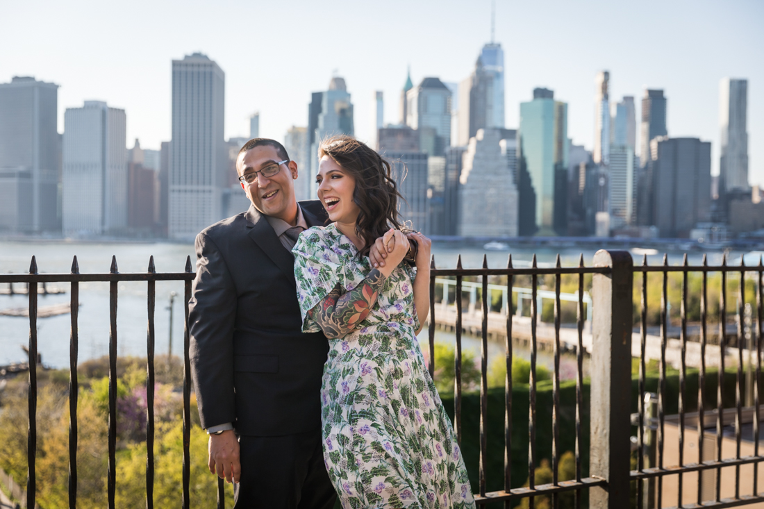 Couple hugging in front of metal fence during a Brooklyn Heights Promenade engagement photo shoot
