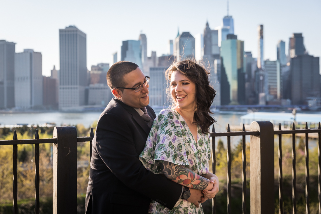 Couple hugging in front of fence and Manhattan skyline