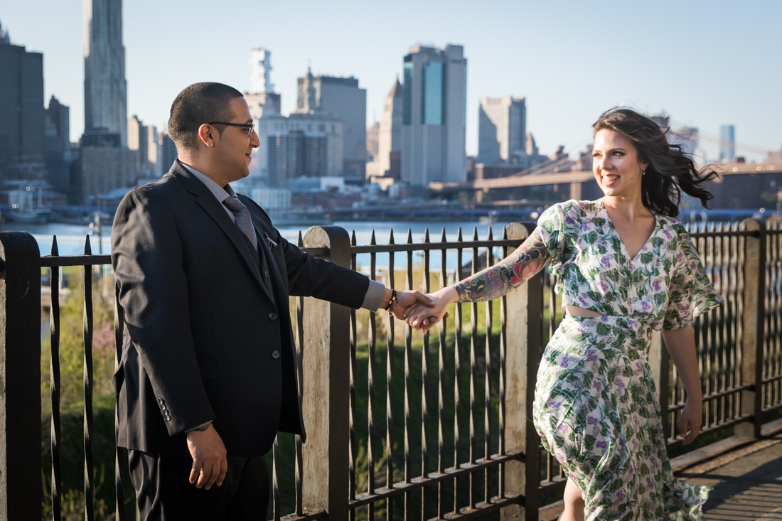 Couple holding hands while dancing during a Brooklyn Heights Promenade engagement photo shoot