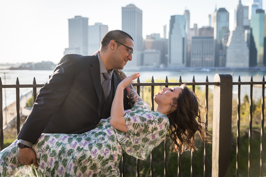 Man dipping woman next to fence during a Brooklyn Heights Promenade engagement photo shoot
