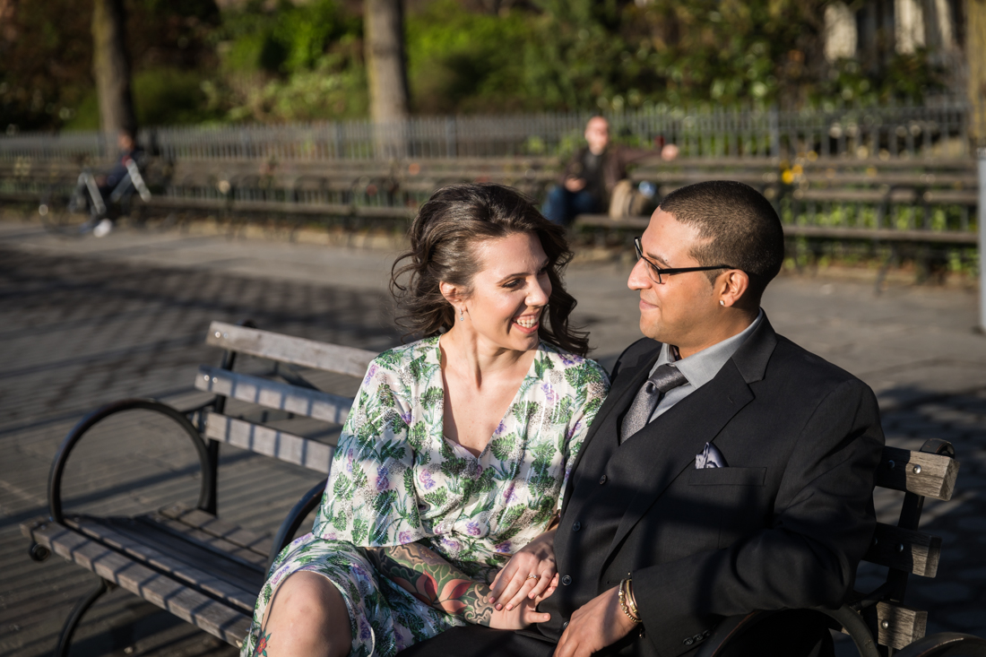 Couple looking at each other while seated on bench during a Brooklyn Heights Promenade engagement photo shoot