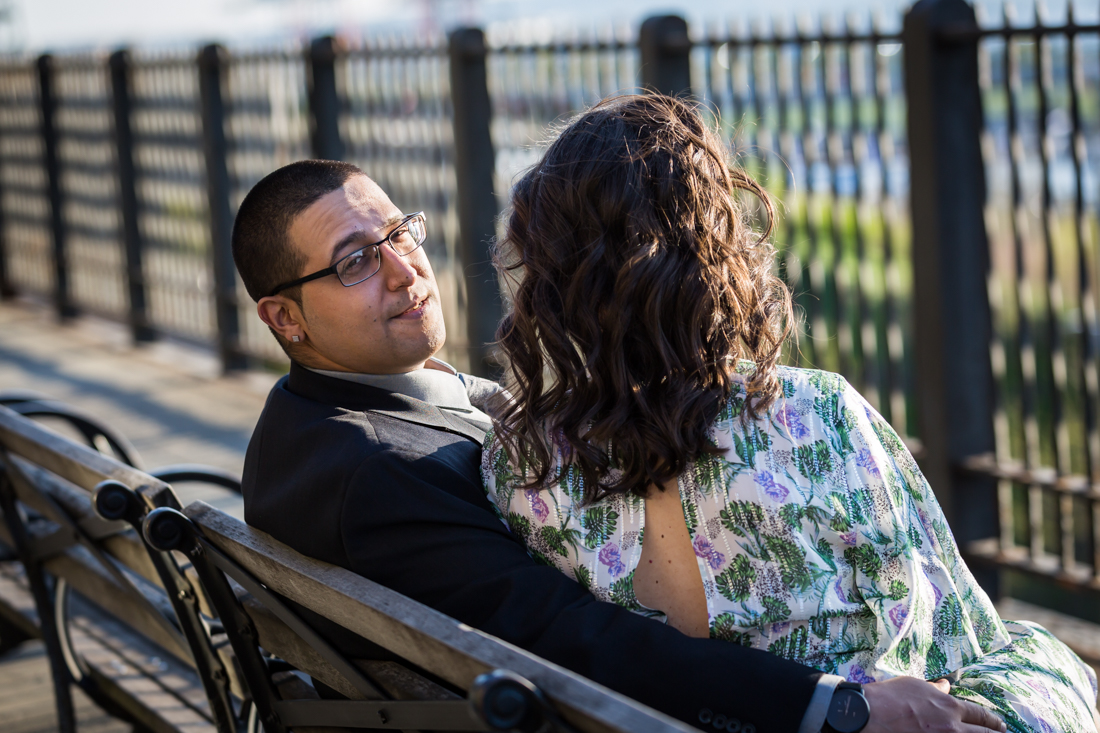 Man seated next to woman on bench during a Brooklyn Heights Promenade engagement photo shoot