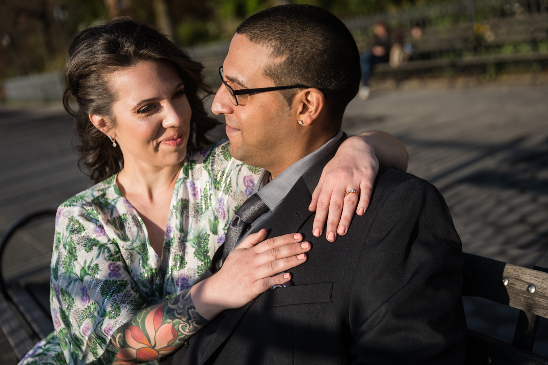 Couple seated on bench during a Brooklyn Heights Promenade engagement photo shoot