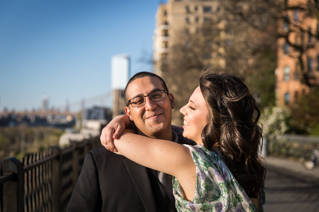 Woman hugging man around the neck during a Brooklyn Heights Promenade engagement photo shoot