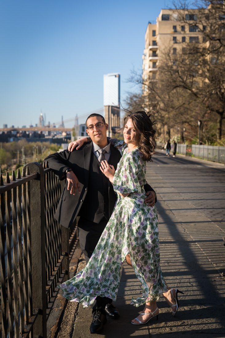 Couple leaning against railing during a Brooklyn Heights Promenade engagement photo shoot