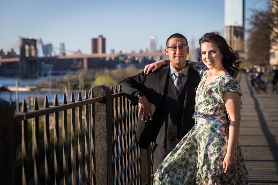 Couple hugging in front of metal railing during a Brooklyn Heights Promenade engagement photo shoot
