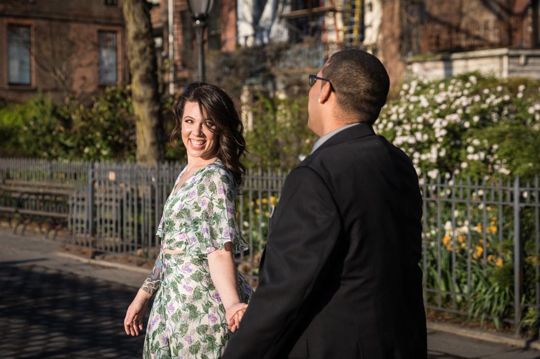 Woman looking back at man during a Brooklyn Heights Promenade engagement photo shoot