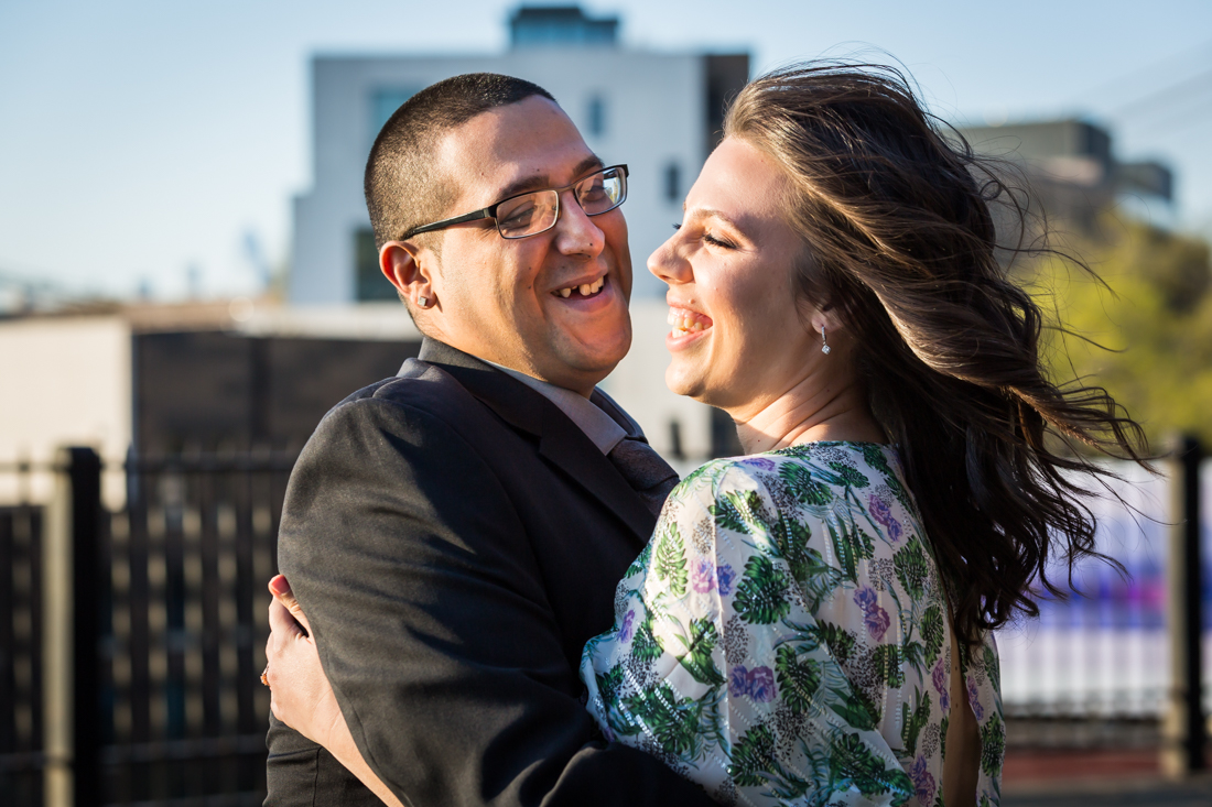 Couple laughing during a Brooklyn Heights Promenade engagement photo shoot