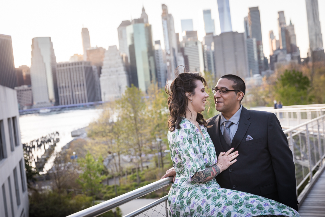 Couple leaning against walkway in front of Manhattan skyline