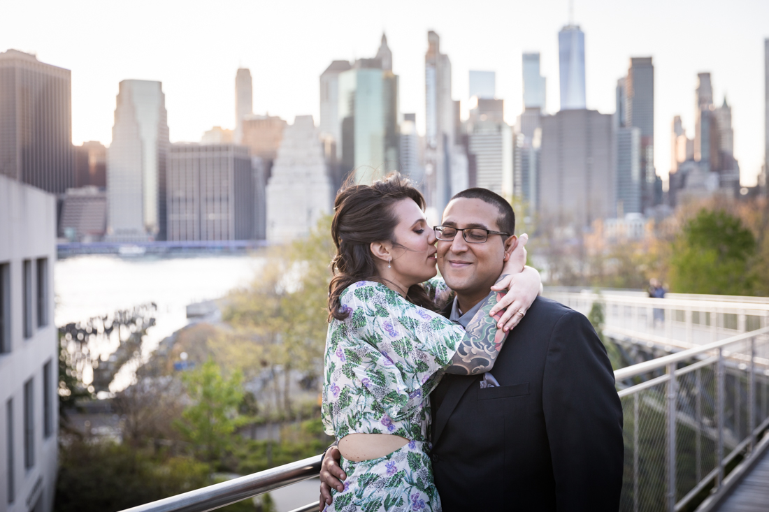 Woman kissing man in front of Manhattan skyline