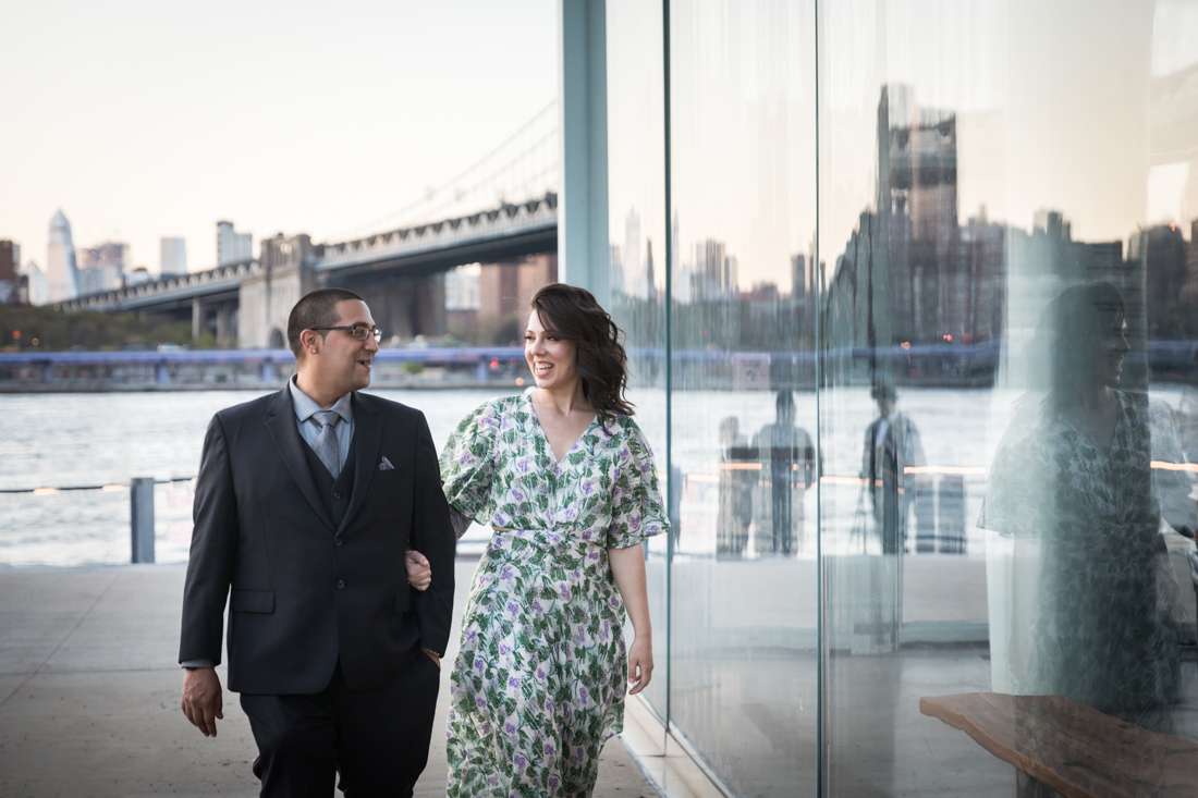 Couple walking in front of glass window during Brooklyn Bridge Park engagement shoot