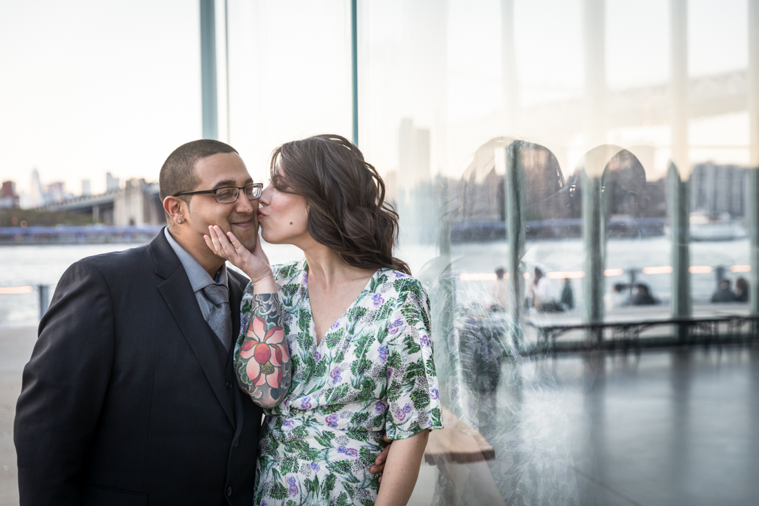 Couple kissing beside glass window during Brooklyn Bridge Park engagement shoot
