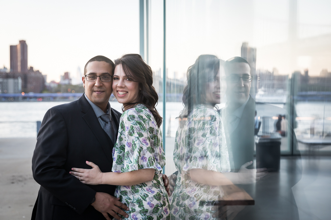 Reflection of couple hugging in glass during Brooklyn Bridge Park engagement shoot