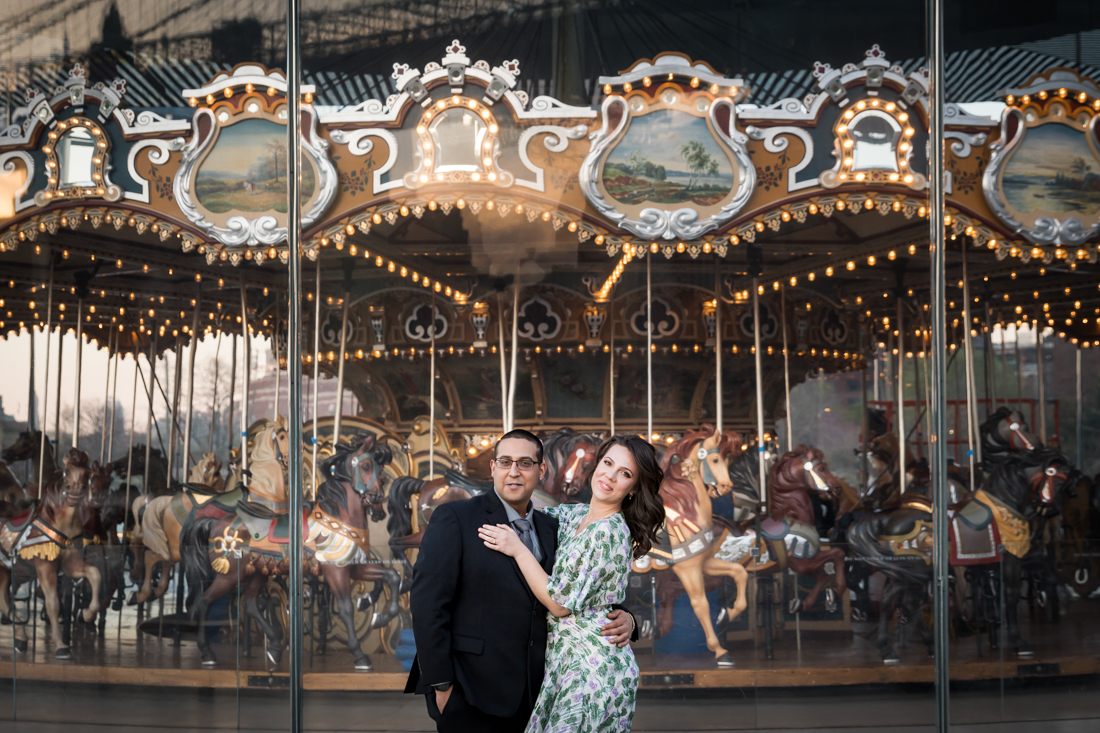 Couple hugging in front of Jane's Carousel during Brooklyn Bridge Park engagement shoot