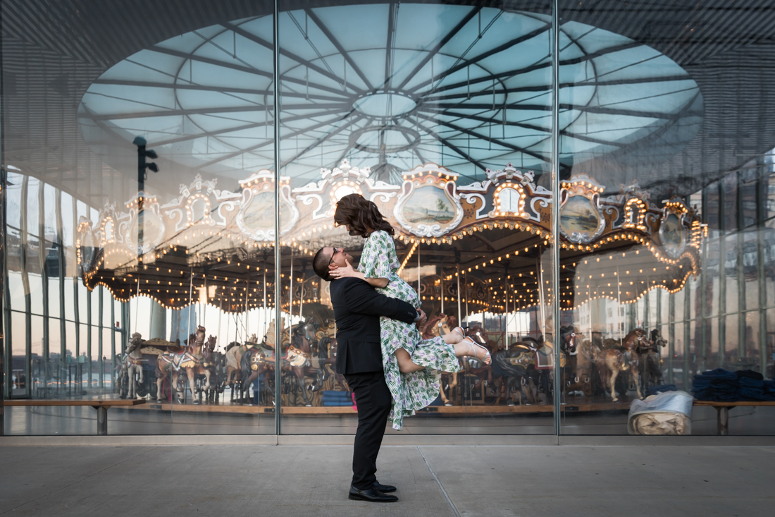 Man lifting woman up in front of Jane's Carousel during Brooklyn Bridge Park engagement shoot