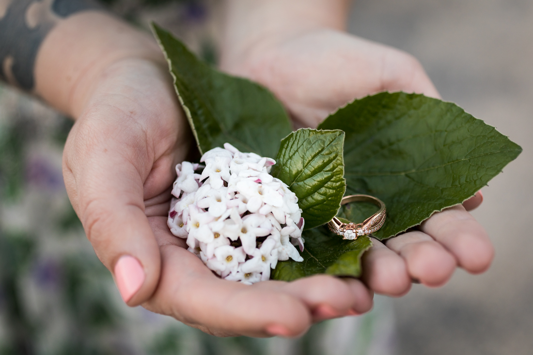 Hands holding white flowers and engagement ring