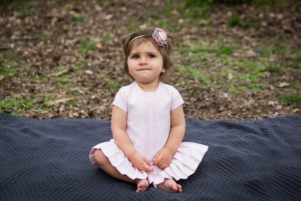 Little girl wearing a pink dress and sitting on a grey blanket