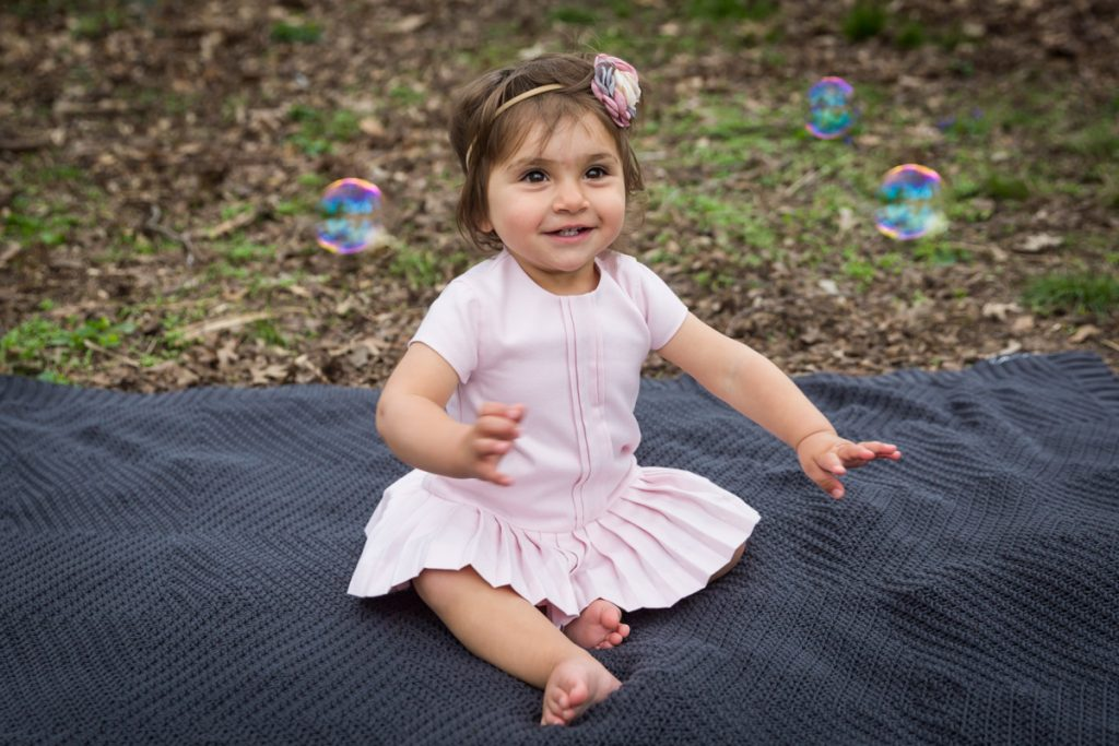 Little girl wearing a pink dress and sitting on a grey blanket with bubbles