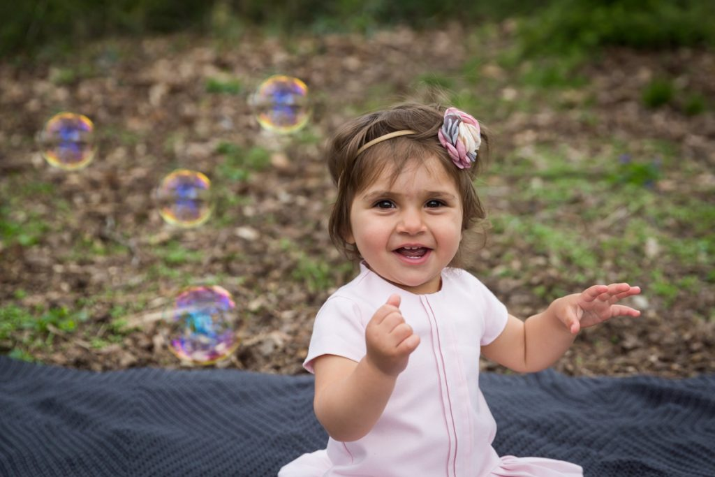Little girl wearing a pink dress and playing with bubbles