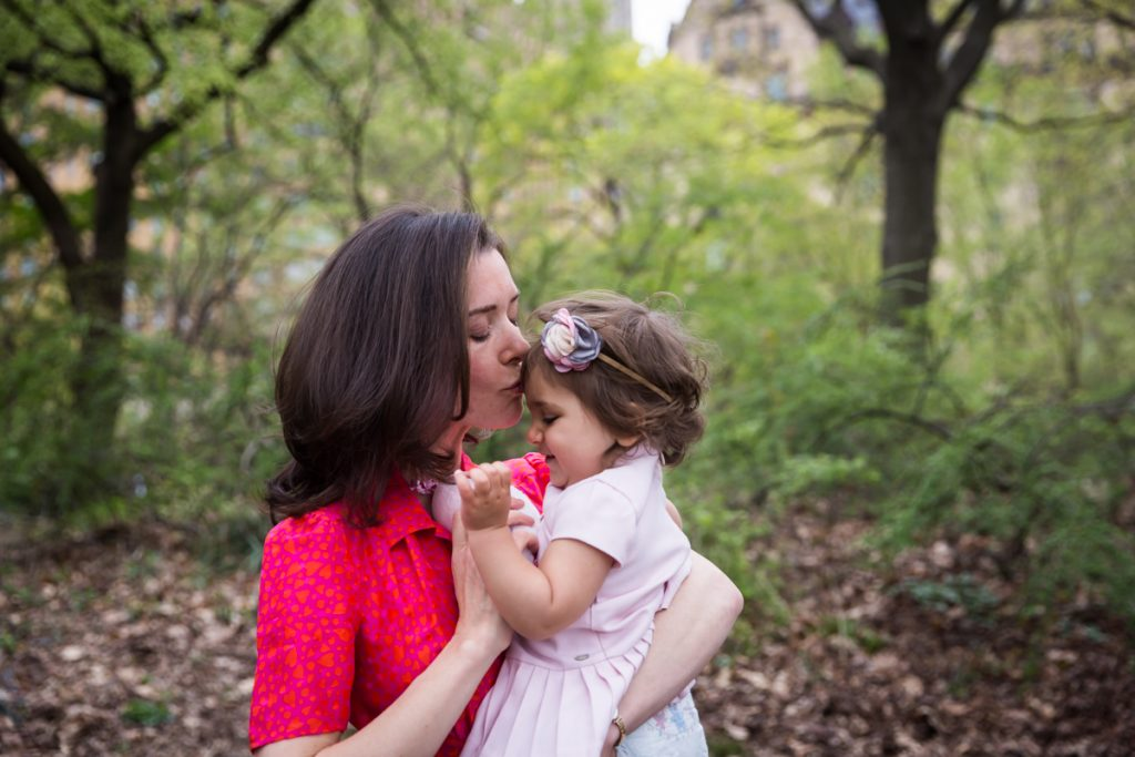 Mother in red dress kissing little girl in pink dress