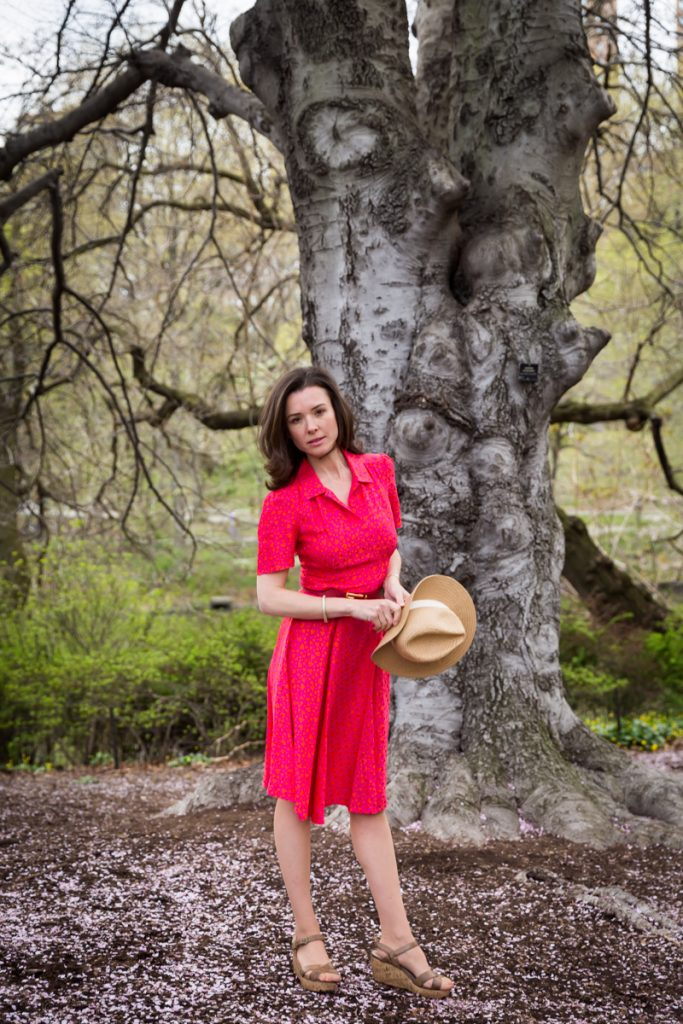 Woman wearing red dress and holding a hat in front of a tree