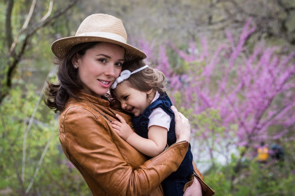 Woman wearing hat and holding baby girl for an article on NYC family portrait location ideas