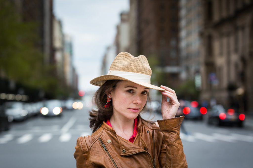 Woman holding on to brim of hat for an article on NYC family portrait location ideas