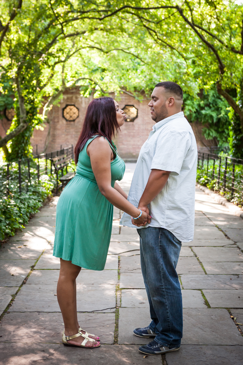 Couple standing in Conservatory Garden walkway holding hands during a Central Park engagement shoot