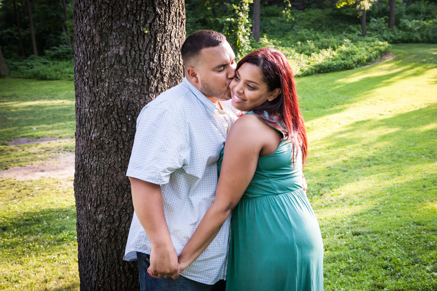 Man kissing woman on cheek beside tree during a Central Park engagement shoot