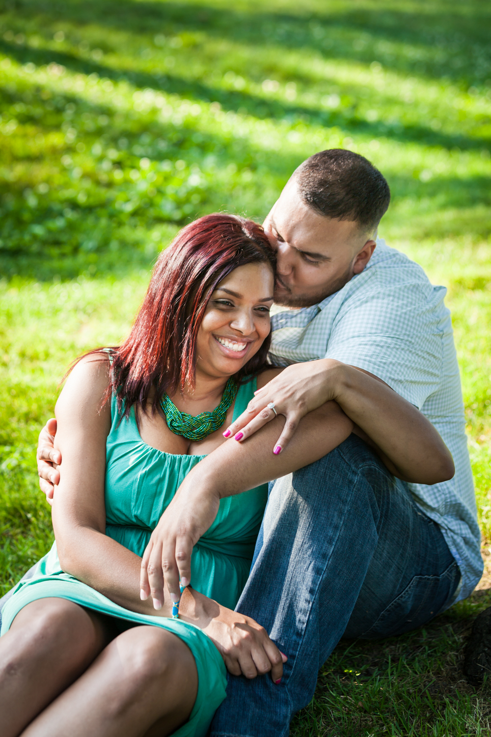 Couple sitting in grass and man kissing woman on side of head during a Central Park engagement shoot