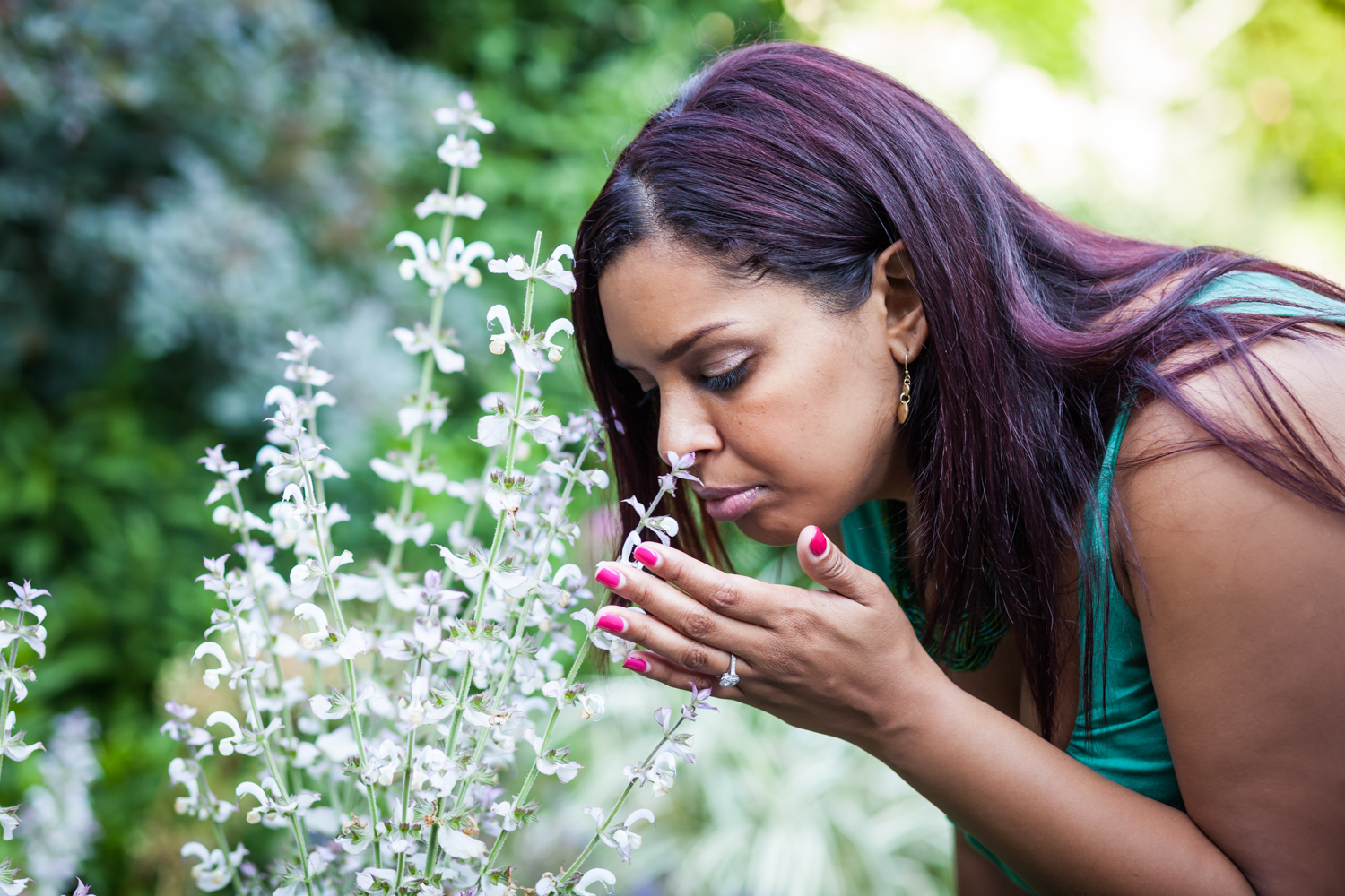 Woman wearing engagement ring leaning down and smelling flower
