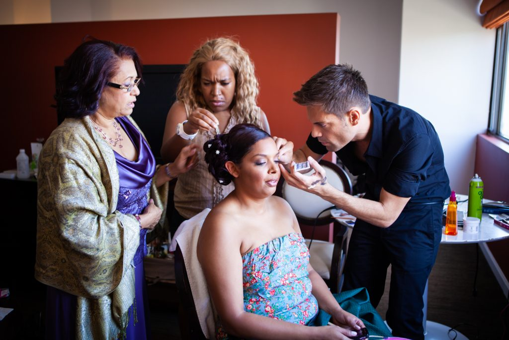 Makeup being applied to a bride sitting