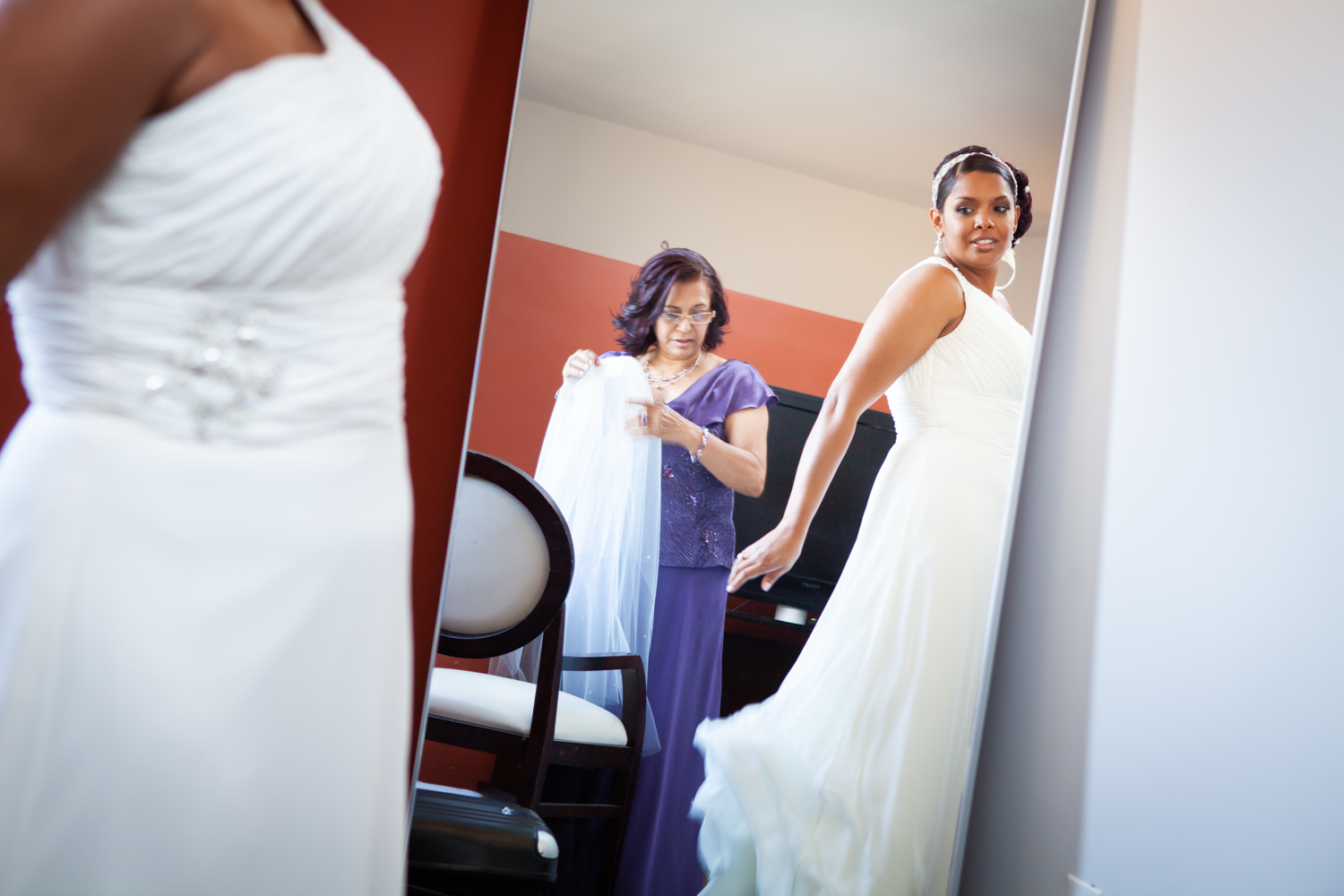 Bride looking at reflection of white dress in mirror