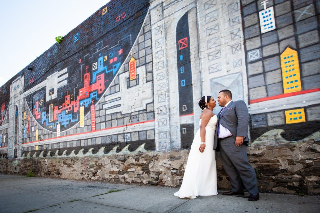 Bride and groom standing in front of colorful graffiti mural before their Attic Studios wedding