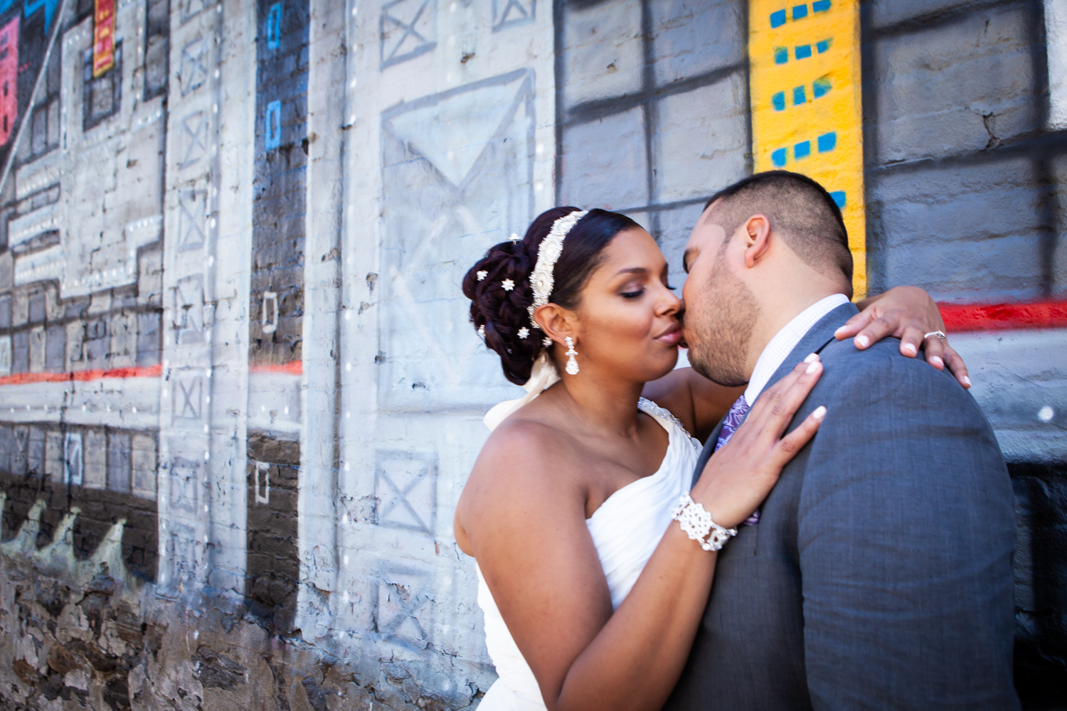 Bride and groom kissing in front of graffiti mural