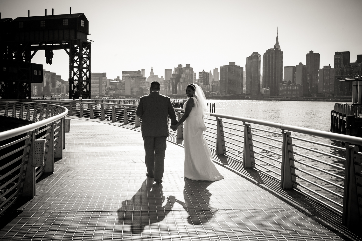 Black and white photo of bride and groom walking in Gantry Plaza State Park
