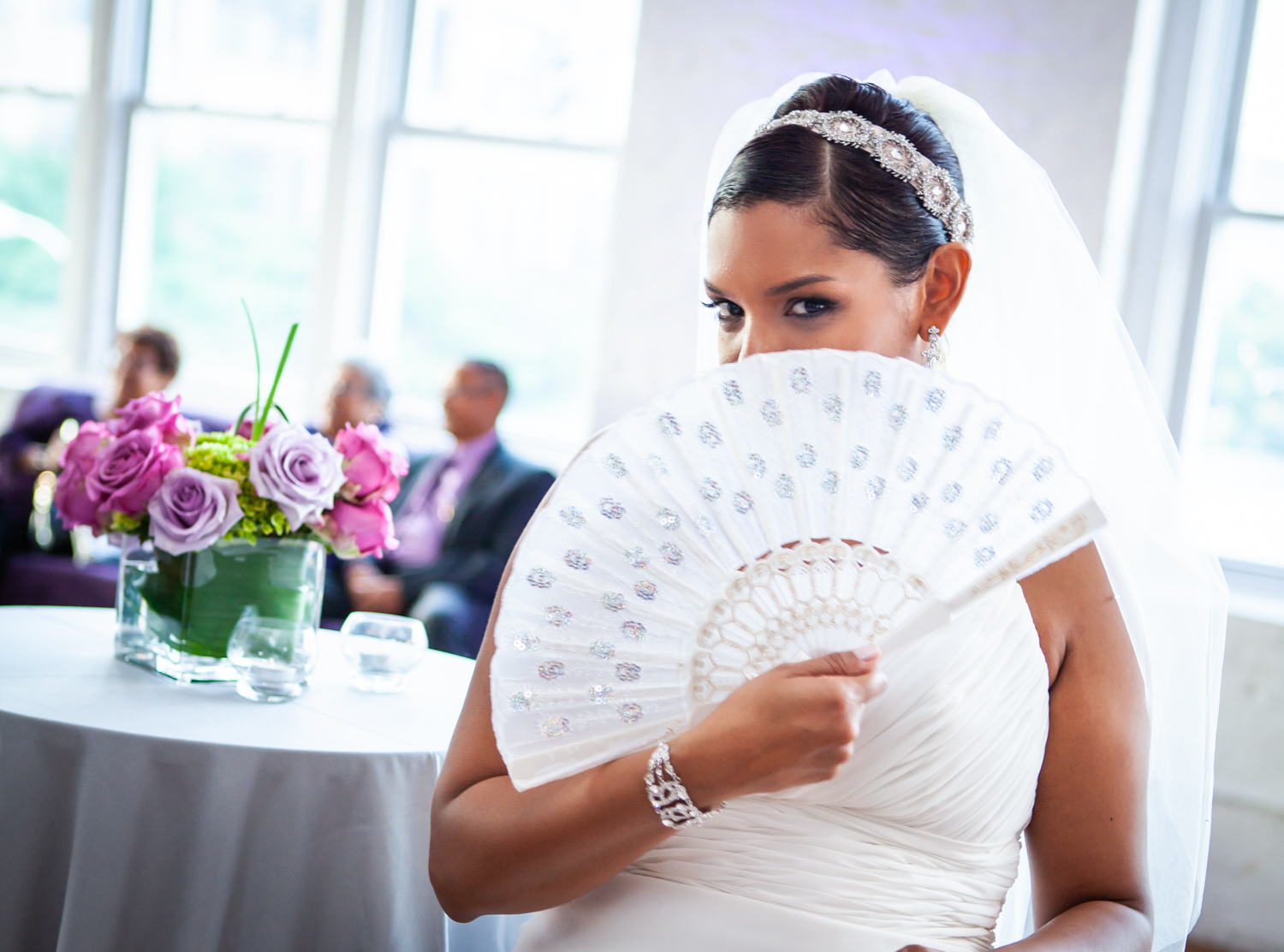 Bride looking over fan at an Attic Studios wedding