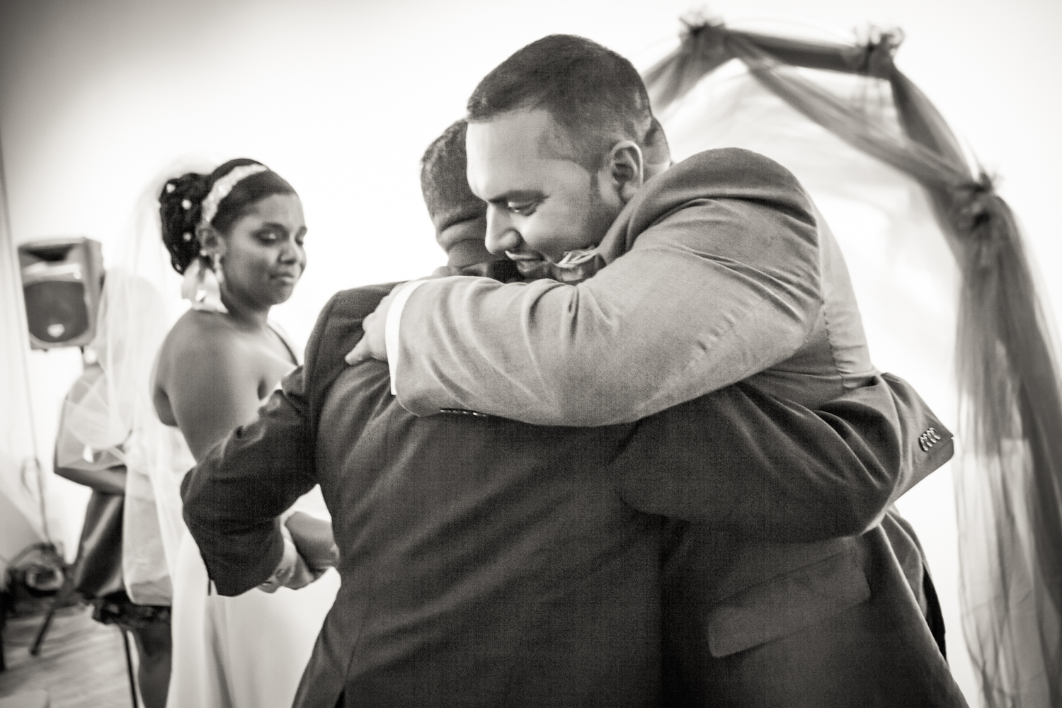 Black and white photo of groom hugging bride's father