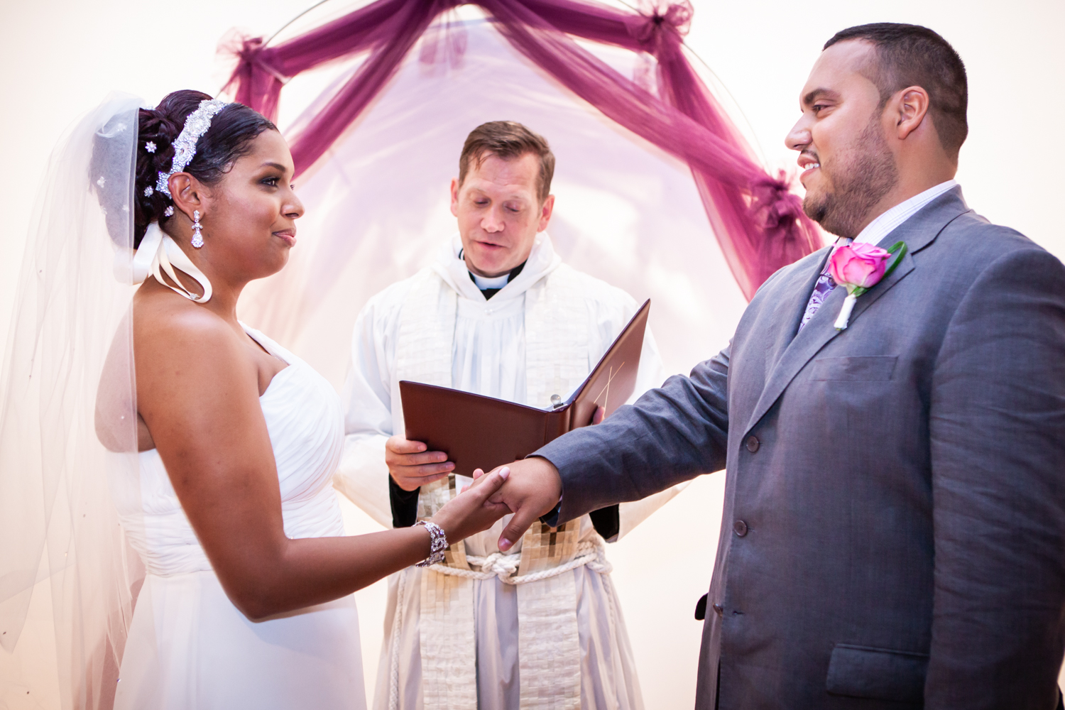 Bride and groom holding hands in front of priest at an Attic Studios wedding