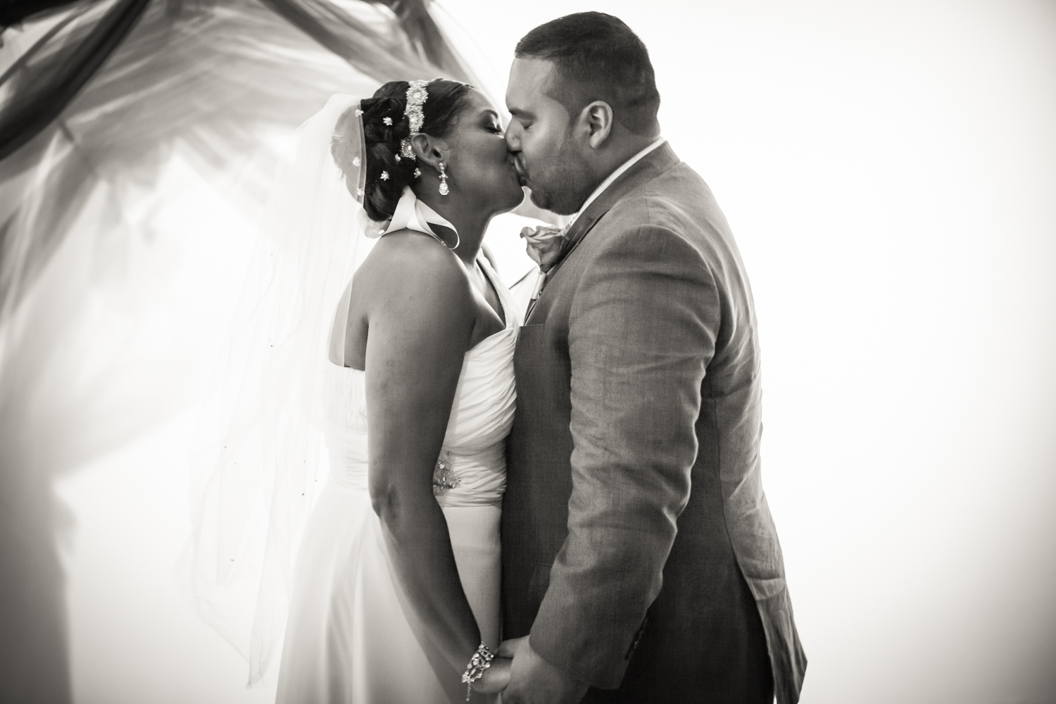 Black and white photo of bride and groom kissing at Attic Studios ceremony