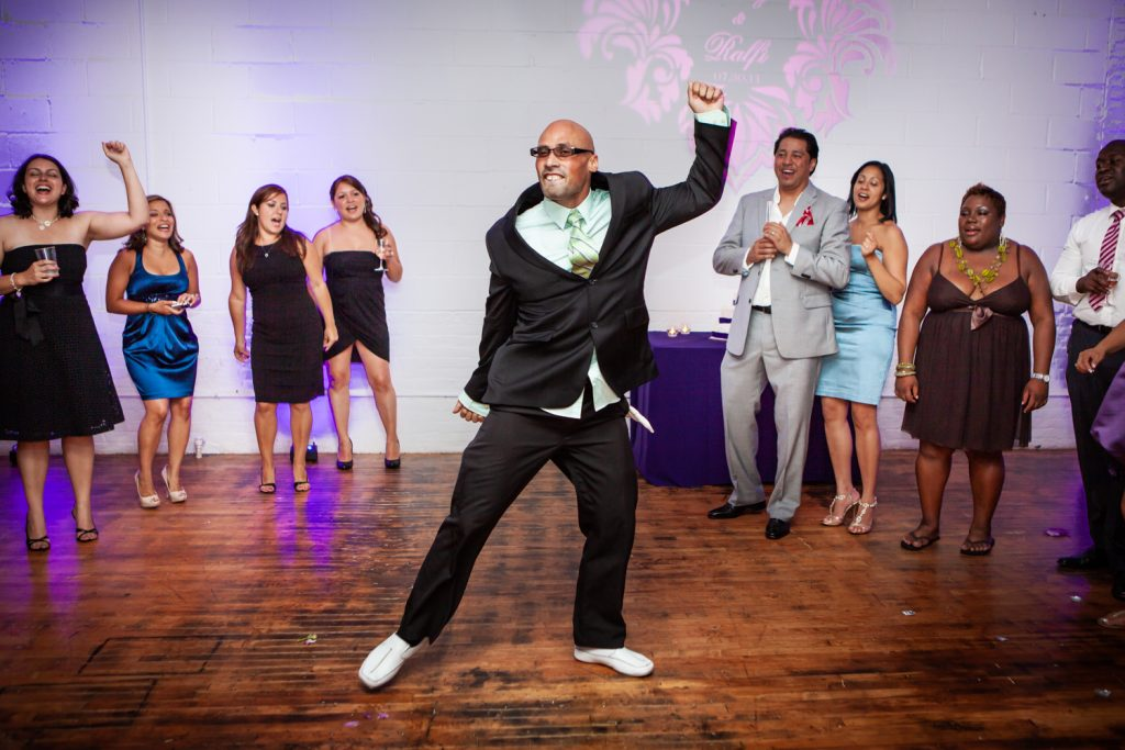 Man dancing in circle of guests at an Attic Studios wedding