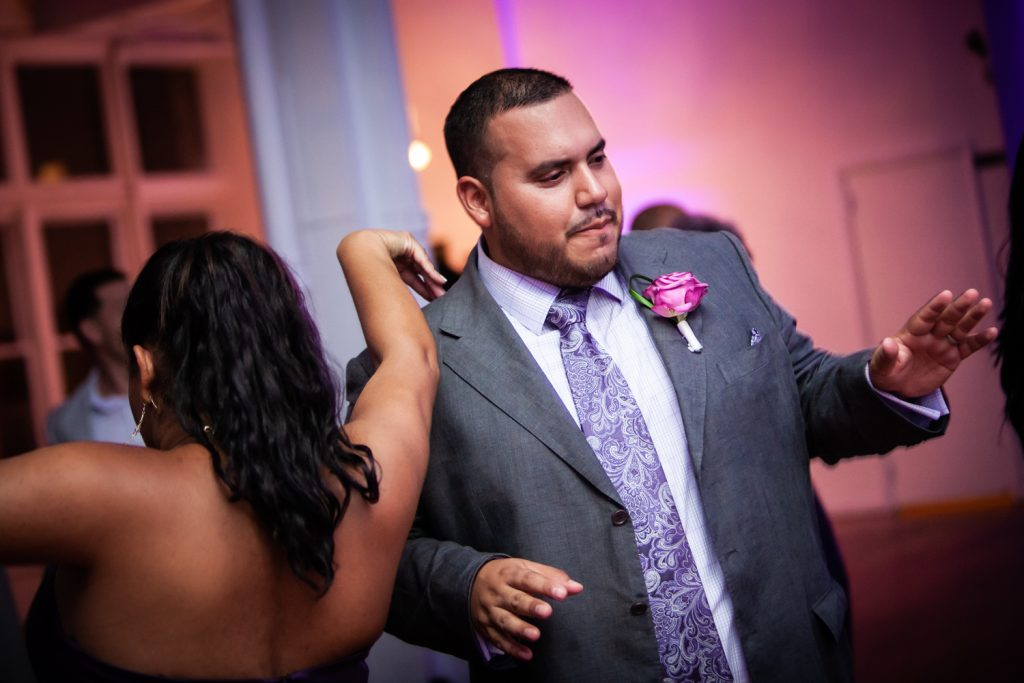 Groom dancing with guest at an Attic Studios wedding
