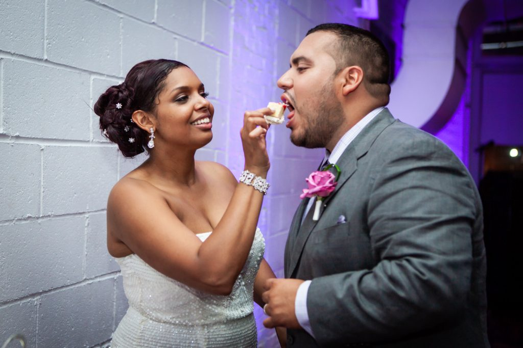 Bride feeding cake to groom at an Attic Studios wedding