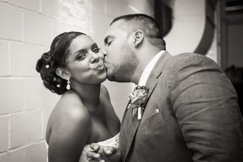 Black and white photo of groom kissing bride on cheek